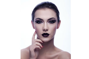 A woman wearing dark eye and lip makeup
